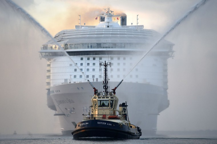 A tug boat leads the way for the world's largest passenger ship, Harmony of the Seas, owned by Royal Caribbean, as it makes her way up Southampton Water, into Southampton, England, Tuesday May 17, 2016, ahead of her maiden cruise. (Andrew Matthews/PA via AP)