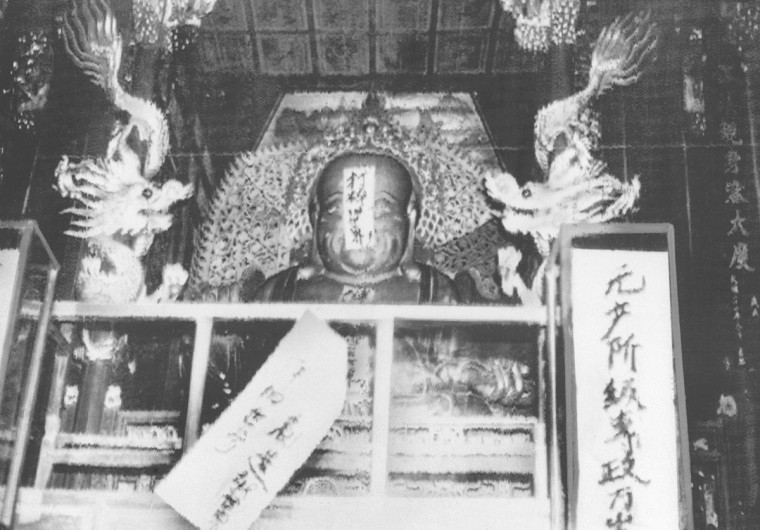 "In this file photo taken Aug. 27, 1966, a buddha statue is covered with signs reading ""Destroy the old world,"" and ""Establish a new world,"" by ultra-patriotic Red Guard who reject ancient Chinese traditions at Lin Yin temple in Hangzhou, eastern China's Zhejiang province. Monday, May 16, 2016 marks the 50th anniversary of a 1966 party meeting that spearheaded the 10-year Cultural Revolution, a violent and frequently chaotic attempt by Mao to reassert his power and revive his party's egalitarian ideals. (AP Photo, File)"