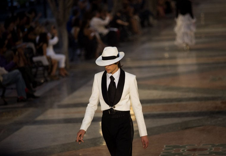 """A model wears a creation from the Karl Lagerfeld """"cruise"""" line for fashion house Chanel, at the Paseo del Prado street in Havana, Cuba, Tuesday, May 3, 2016. With the heart of the Cuban capital effectively privatized by an international corporation under the watchful eye of the Cuban state, the premiere of Chanel 2016/2017 """"cruise"""" line offered a startling sight in a country officially dedicated to social equality and the rejection of material wealth. (AP Photo/Ramon Espinosa)"""
