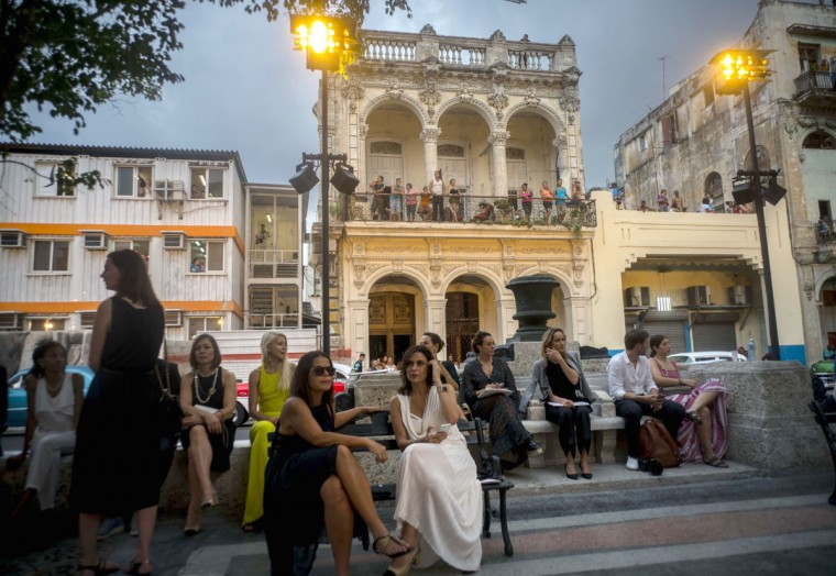 """People attend the presentation of fashion designer Karl Lagerfeld's """"cruise"""" line for fashion house Chanel, at the Paseo del Prado street in Havana, Cuba, Tuesday, May 3, 2016. With the heart of the Cuban capital effectively privatized by an international corporation under the watchful eye of the Cuban state, the premiere of Chanel 2016/2017 """"cruise"""" line offered a startling sight in a country officially dedicated to social equality and the rejection of material wealth. (AP Photo/Ramon Espinosa)"""