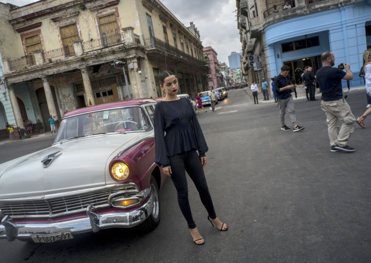 """A model poses in front of a vintage American car as she arrives to the presentation of fashion designer Karl Lagerfeld's """"cruise"""" line for fashion house Chanel, at the Paseo del Prado street in Havana, Cuba, Tuesday, May 3, 2016. With the heart of the Cuban capital effectively privatized by an international corporation under the watchful eye of the Cuban state, the premiere of Chanel 2016/2017 """"cruise"""" line offered a startling sight in a country officially dedicated to social equality and the rejection of material wealth. (AP Photo/Ramon Espinosa)"""