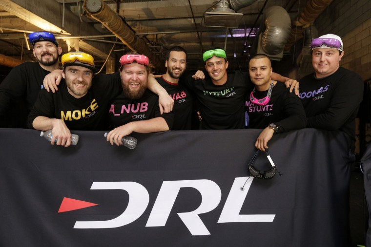 In this March 18, 2016, photo, pilots from the Drone Racing League, from left to right: Chris Haskins, Travis McIntyre, Zach Thayer,Jordan Temkin, Shaun Taylor, Matty Stuntz, Matthew Augustine, and Steve Zoumas pose for a photo at a vacant mall in Hawthorne, Calif. ( AP Photo/Nick Ut)