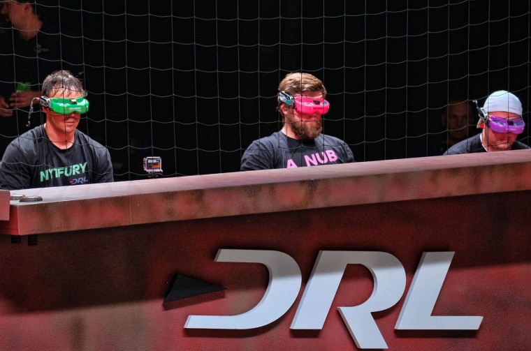 In this March 19, 2016, photo, Drone Racing League pilots Shaun Taylor, from Albuquerque, N.M., left, Zach Thayer, from Laguna Niguel, Calif., center, and Steve Zoumas from Wading River, N.Y., operate their drones during a DRL competition at a vacant mall in Hawthorne, Calif. (AP Photo/Richard Vogel)