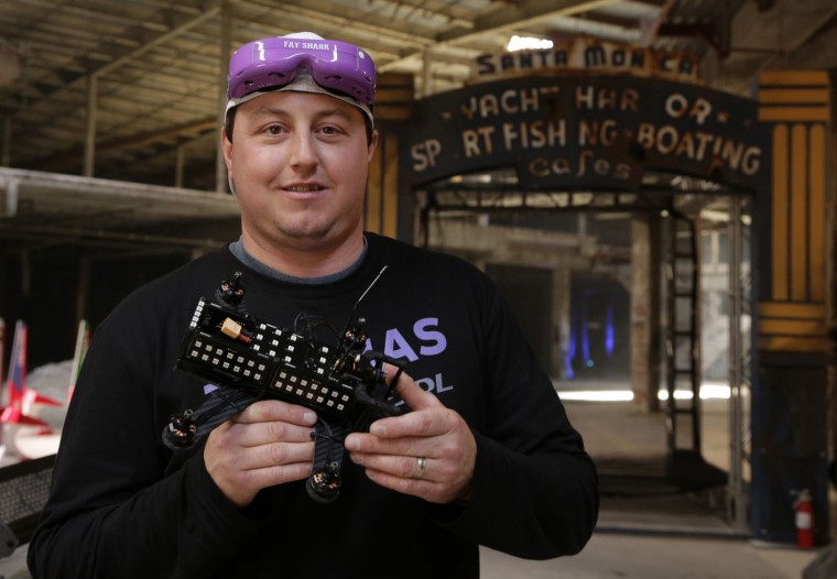 In this March 18, 2016, photo, Steve Zoumas, from Wading River, N.Y., poses for a photo with his drone at a vacant mall in Hawthorne, Calif. Drone racing leagues would love to follow sports like poker into the mainstream with big TV audiences and sponsorships. But getting sponsors and fans is also a race against time. (AP Photo/Nick Ut)