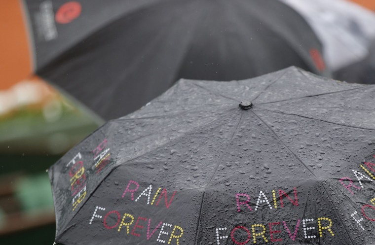 "Spectators sit under an umbrella reading ""Rain Forever"" shortly before all first round matches of the French Open tennis tournament were delayed till the next day because of the rain at Roland Garros stadium in Paris, France, Sunday, May 22, 2016. (AP Photo/Michel Euler)"