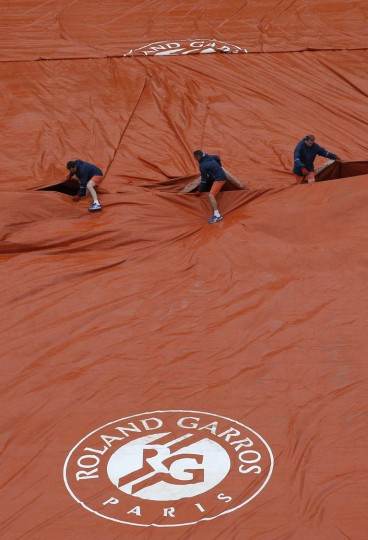 Stadium employees protect the court just after Lucie Safarova of the Czech Republic defeated Vitalia Diatchenko of Russia during their first round match of the French Tennis Open at the Roland Garros stadium Sunday, May 22, 2016 in Paris. Safarova won 6-0, 6-2. (AP Photo/Christophe Ena)