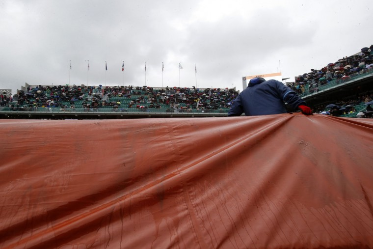 A stadium employee pulls a cover onto center court as rain delays the first round match of the French Open tennis tournament where Japan's Kei Nishikori plays Italy's Simone Bolelli at the Roland Garros stadium, Sunday May 22, 2016 in Paris. (AP Photo/Michel Euler)