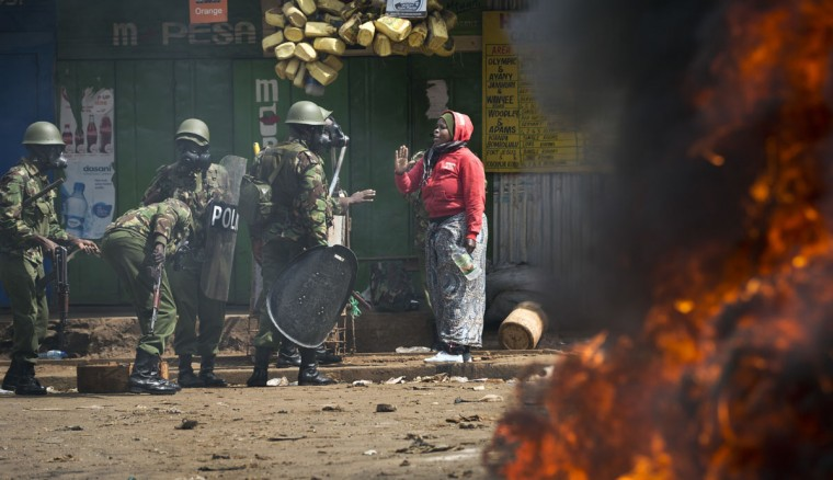 A woman resident talks with police as they engage in running battles between police firing tear gas and protesters throwing rocks, in the Kibera slum of Nairobi, Kenya Monday, May 23, 2016. Kenya's police shot, beat and tear gassed opposition demonstrators across the country who tried to gather to call for the electoral commission to be dissolved due to allegations of bias and corruption. (AP Photo/Ben Curtis)