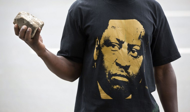 An opposition protester wearing a T-shirt of opposition leader Raila Odinga holds a rock, as he and others tried to gather outside the offices of the electoral commission before being tear-gassed away by police, in downtown Nairobi, Kenya Monday, May 23, 2016. Kenya's police shot, beat and tear gassed opposition demonstrators across the country who tried to gather to call for the electoral commission to be dissolved due to allegations of bias and corruption. (AP Photo/Ben Curtis)