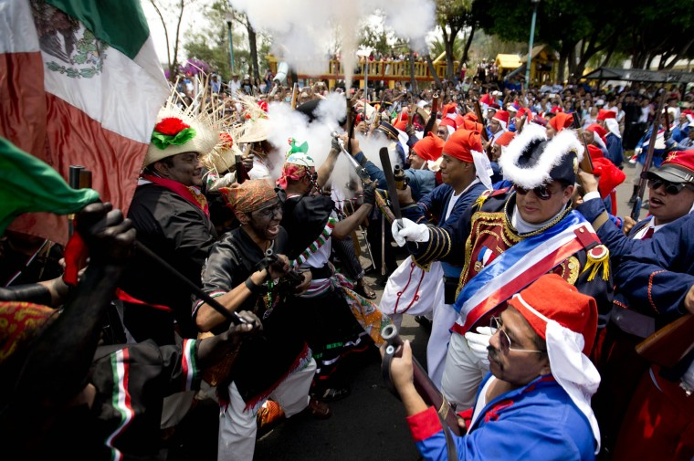 Local residents dressed as Zacapoaxtla Indians, left, and French soldiers, right, clash during a reenactment of the battle of Puebla during Cinco de Mayo celebrations, in the Penon de los Banos neighborhood of Mexico City, Wednesday, May 5, 2016. Cinco de Mayo commemorates the victory of an ill-equipped Mexican army over French troops in Puebla on May 5, 1862. (AP Photo/Eduardo Verdugo)