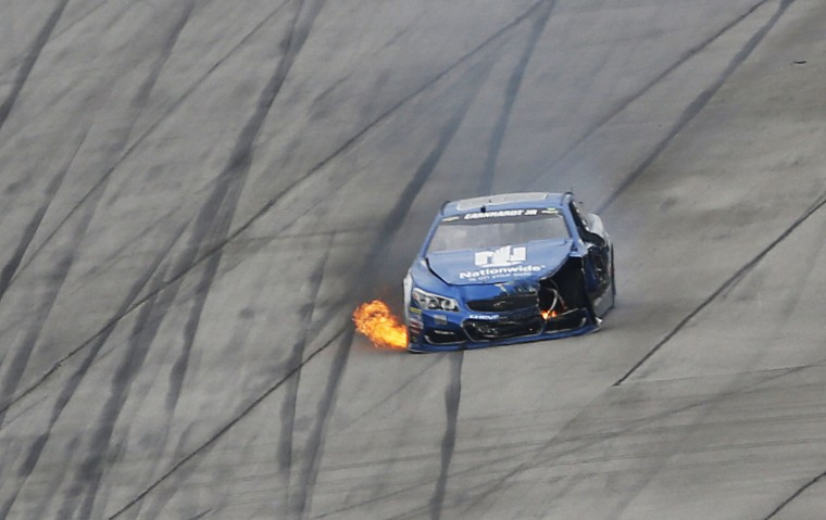 Flames trail from the car of Dale Earnhardt Jr. leaves the track after he wrecked near Turn 2 during the NASCAR Talladega auto race at Talladega Superspeedway, Sunday, May 1, 2016, in Talladega, Ala. (AP Photo/John Bazemore)
