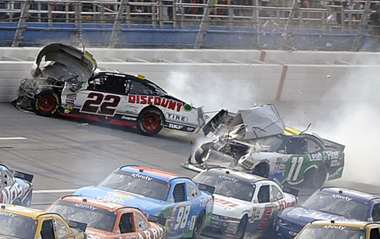 Joey Logano (22) slides near the wall after Blake Koch (11) ran into him shortly before the finish during NASCAR Xfinity Series auto race at Talladega Superspeedway, Saturday, April 30, 2016, in Talladega, Ala. Logano had been spun by Elliott Sadler, hit the wall, and was then hit by Koch. (AP Photo/Matthew Bishop)