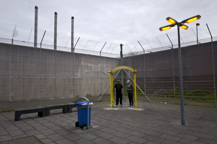 Algerian migrant Mohammed Ben Salem, 36, left, and Libyan Amine Oshi, 22, smoke a cigarette at a yard of the former prison of De Koepel in Haarlem, Netherlands. With crime declining in the Netherlands, the country is looking at new ways to fill its prisons. The government has let Belgium and Norway put prisoners in its empty cells and now, amid the huge flow of migrants into Europe, several Dutch prisons have been temporarily pressed into service as asylum seeker centers. (AP Photo/Muhammed Muheisen)