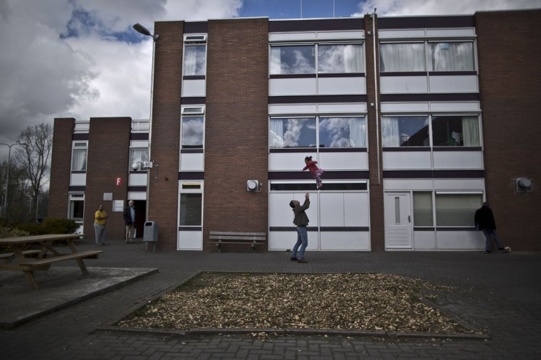 Amigrant plays with a girl at the former prison of Westlingen in Heerhugowaard northwestern Netherlands. The Dutch government has let Belgium and Norway put prisoners in its empty cells and now, amid the huge flow of migrants into Europe, several Dutch prisons have been temporarily pressed into service as asylum seeker centers. (AP Photo/Muhammed Muheisen)