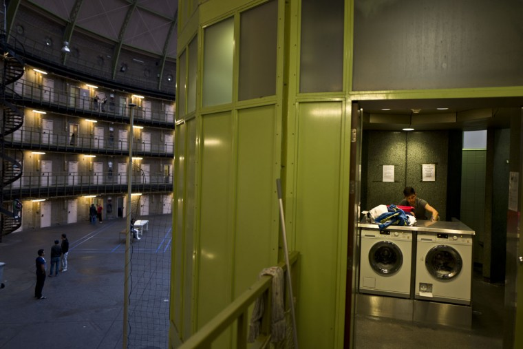 Afghan refugee Siratullah Hayatullah, 23, uses a washing room in the former prison of De Koepel in Haarlem, Netherlands. The Dutch government has let Belgium and Norway put prisoners in its empty cells and now, amid the huge flow of migrants into Europe, several Dutch prisons have been temporarily pressed into service as asylum seeker centers. (AP Photo/Muhammed Muheisen)