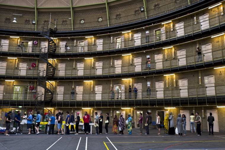 Refugees and migrants line up to receive their lunch at the former prison of De Koepel in Haarlem, Netherlands. With crime declining in the Netherlands, the country is looking at new ways to fill its prisons. The government has let Belgium and Norway put prisoners in its empty cells and now, amid the huge flow of migrants into Europe, several Dutch prisons have been temporarily pressed into service as asylum seeker centers. (AP Photo/Muhammed Muheisen)