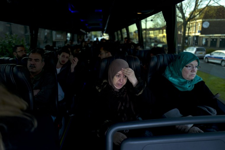 Iraqi refugee Fatima Hussein, 65, reacts while she and others wait in a bus heading to have a government interview for their asylum seeking process outside the former prison of De Koepel in Haarlem, Netherlands. With crime declining in the Netherlands, the country is looking at new ways to fill its prisons. The government has let Belgium and Norway put prisoners in its empty cells and now, amid the huge flow of migrants into Europe, several Dutch prisons have been temporarily pressed into service as asylum seeker centers. (AP Photo/Muhammed Muheisen)
