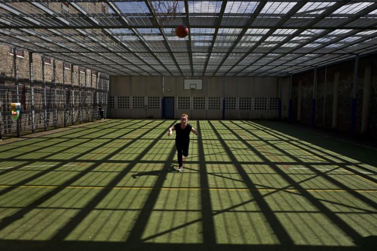 Mongolian migrant Naaran Baatar, 40, plays basketball at a yard of the former prison of De Koepel in Haarlem, Netherlands. (AP Photo/Muhammed Muheisen)
