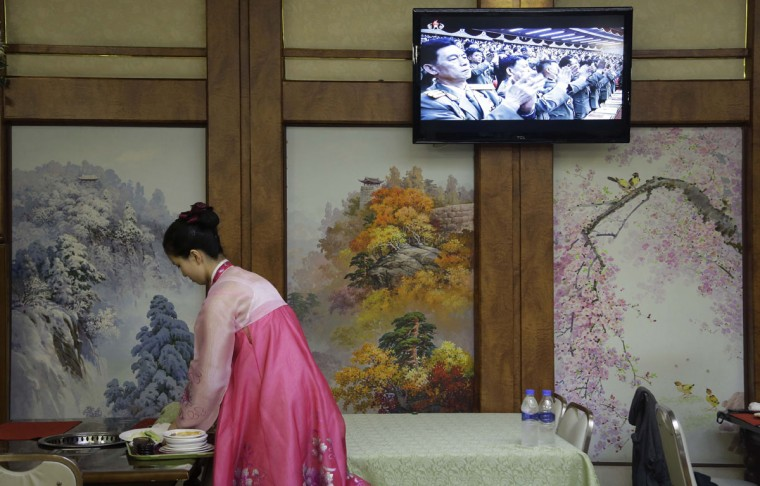 A waitress clears a table while a broadcast of the second day of the 7th Congress of the Workers' Party of Korea is shown on local television on Saturday, May 7, 2016, in Pyongyang, North Korea. North Korea's ruling party is preparing to bestow its top title on leader Kim Jong Un, another clear sign that the third heir to North Korea's dynasty of Kims is firmly in control despite his country's deepening international isolation over one of his key ambitions, to keep developing more and better nuclear weapons. (AP Photo/Wong Maye-E)