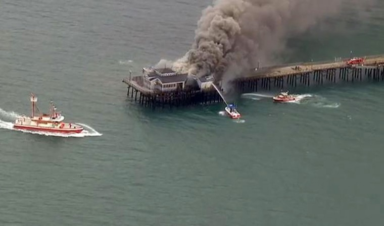 In this image made from video provided by KABC-TV, firefighters attack a fire on the Seal Beach pier in Seal Beach, Calif. on Friday, May 20, 2016. A fire is burning on a former restaurant on Southern California's Seal Beach Pier. The blaze erupted early Friday at the end of the long wooden pier southeast of Los Angeles. Harbor patrol boats are attacking the flames with streams from water cannons while firefighters direct streams from hoses on the pier. (KABC-TV via AP)