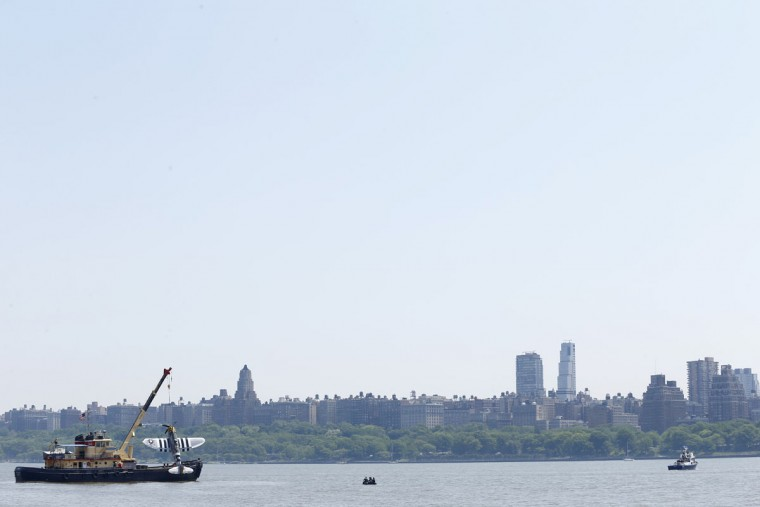 Officials remove a plane out of the Hudson River a day after it crashed, Saturday, May 28, 2016, in North Bergen, N.J. The World War II vintage P-47 Thunderbolt aircraft crashed into the river Friday, May 27 killing its pilot. (AP Photo/Julio Cortez)