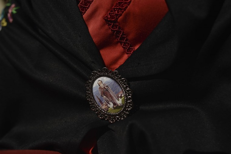 A participant in the ''Bread Procession of the Saint'', holds a medallion with a figure of Domingo de La Calzada Saint in the ceremony in honor of this Saint (1019-1109), in Santo Domingo de La Calzada, northern Spain, Wednesday, May 11, 2016. Every year during spring season, ''Las Doncellas'' (White Virgins), hold on their head a basket covered with white cloth while they walk through of this old village in honor of the saint. (AP Photo/Alvaro Barrientos)
