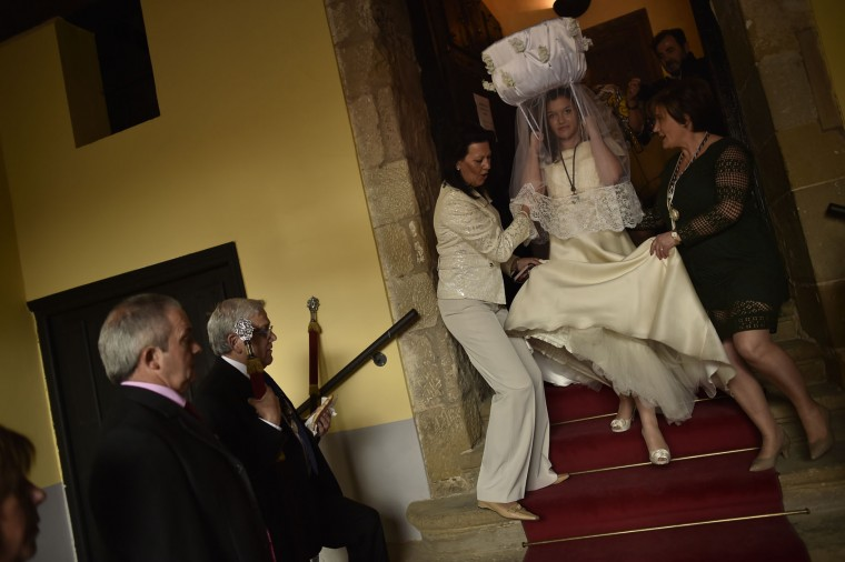 A participant in the ''Bread Procession of the Saint'' walks down the stairs before taking part in a ceremony in honor of Domingo de La Calzada Saint (1019-1109), in Santo Domingo de La Calzada, northern Spain, Wednesday, May 11, 2016. Every year during spring season, ''Las Doncellas'' (White Virgins), hold a basket on their head covered with white cloth while they walk along this old village in honor of the saint. (AP Photo/Alvaro Barrientos)