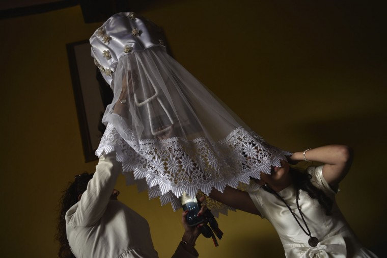 A participant of the ''Bread Procession of the Saint'', is helped as she takes part in the ceremony in honor of Domingo de La Calzada Saint (1019-1109) in Santo Domingo de La Calzada, northern Spain, Wednesday, May 11, 2016. Every year during spring season, ''Las Doncellas'' (White Virgins), hold on their head a basket covered with white cloth while they walk through this old village in honor of the saint. (AP Photo/Alvaro Barrientos)