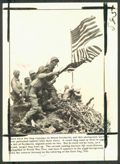 """""""There were two flag raisings at Iwo Jima's Mount Suribachi, and this photograph from 'Strong Men Armed,' tells their story. A small flag went up to signal Suribachi's fall. It could not be seen from the base of the mountains, so a larger flag was raised. The second raising was the one shown in the photograph that became famous. In this picture the first flag is about to be furled as the second one flies."""""""