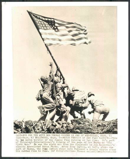 """Hollywood, Sept. 7--MOVIE VERSION OF THE FLAG RAISING--This is the movie version of the famous flag raising at Iwo Jima. It's part of Universal-International's filming of the saga of Ira Hayes as 'The Sixth Man.' He was the sixth man from the flagstaff in Joe Rosenthal's classic Associated Press Photo. Actor Tony Curtis, at left, plays the part of Hayes, the Pima Indian whose life followed a tragic course after his sudden rise to fame."""" (AP Wirephoto dated September 7, 1960)."""