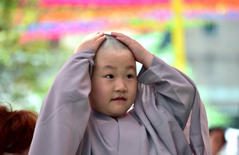 A South Korean child reacts after having his head shaved by Buddhist monks during a ceremony entitled 'Children Becoming Buddhist Monks', at the Jogye temple in Seoul on May 2, 2016. (JUNG YEON-JE/AFP/Getty Images)