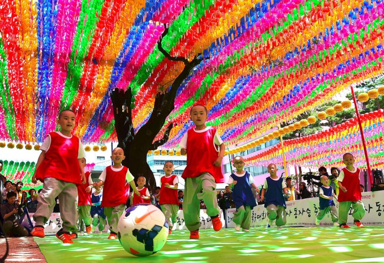 Young South Korean novice monks play soccer under lotus lanterns during their training program entitled 'Children Becoming Buddhist Monks' at the Jogye Temple in Seoul on May 4, 2016. (JUNG YEON-JE/AFP/Getty Images)