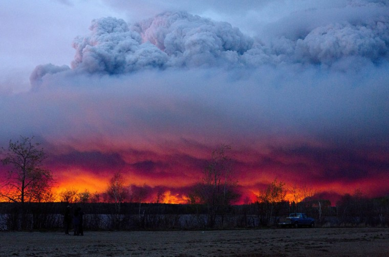 A wildfire moves towards the town of Anzac from Fort McMurray, Alberta., on Wednesday May 4, 2016. Alberta declared a state of emergency Wednesday as crews frantically held back wind-whipped wildfires. Unseasonably hot temperatures combined with dry conditions have transformed the boreal forest in much of Alberta into a tinder box. (Jason Franson/The Canadian Press via AP)