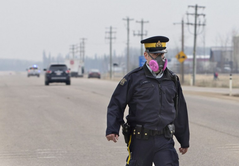 A police officer wears a mask while controlling a roadblock near a wildfire in Fort McMurray, Alberta, Canada on Thursday, May 5, 2016. Raging wildfires in the Canadian province of Alberta have moved south, forcing three more communities to evacuate and an emergency operations center to move again , aking it far from the devastated oil sands city of Fort McMurray. (Jason Franson/The Canadian Press via AP)