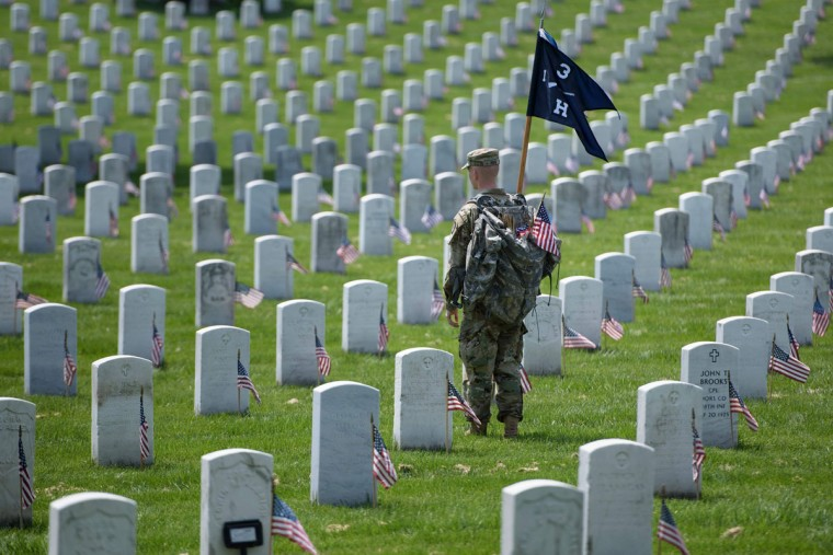 A member of the US Army looks on after placing American flags at graves at Arlington National Cemetery May 26, 2016 in Arlington, Virginia in preparation for Memorial Day. (BRENDAN SMIALOWSKI/AFP/Getty Images)