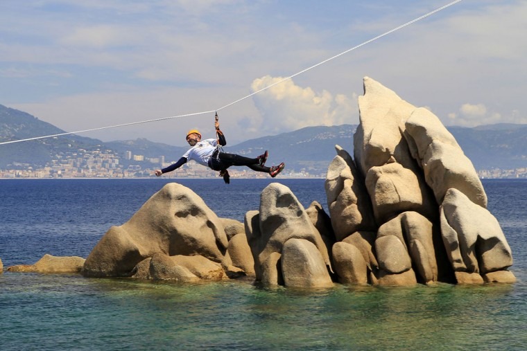 A racer rides a zip line over rocks during a coastering session during the 20th Corsica Raid race in Porticcio along the Gulf of Ajaccio on June 8, 2016 on the French island of Corsica. (PASCAL POCHARD-CASABIANCA/AFP/Getty Images)