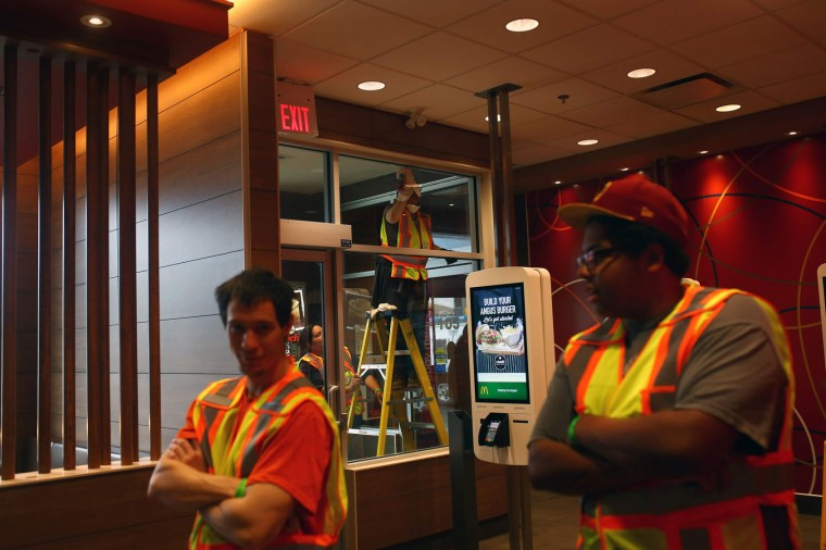Workers clean a McDonald's in Timberlea, a neighbourhood of Fort McMurray, Alberta, on June 1, 2016. Tens of thousands of Fort McMurray residents were expected to begin trickling back into the Canadian oil city ravaged by wildfires Wednesday after the blaze was declared no longer a threat. (Cole Burston/AFP/Getty Images)