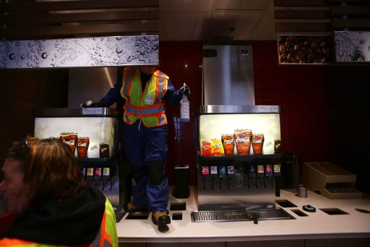 Workers clean a McDonald's in Timberlea, a neighbourhood of Fort McMurray, Alberta on June 1, 2016. Tens of thousands of Fort McMurray residents were expected to begin trickling back into the Canadian oil city ravaged by wildfires Wednesday after the blaze was declared no longer a threat. (Cole Burston/AFP/Getty Images)