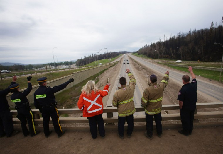Firefighters and RCMP officers greet Fort McMurray residents from an overpass on Highway 63 just outside Fort McMurray, Alberta on June 1, 2016. Tens of thousands of Fort McMurray residents were expected to begin trickling back into the Canadian oil city ravaged by wildfires Wednesday after the blaze was declared no longer a threat. (Cole Burston/AFP/Getty Images)