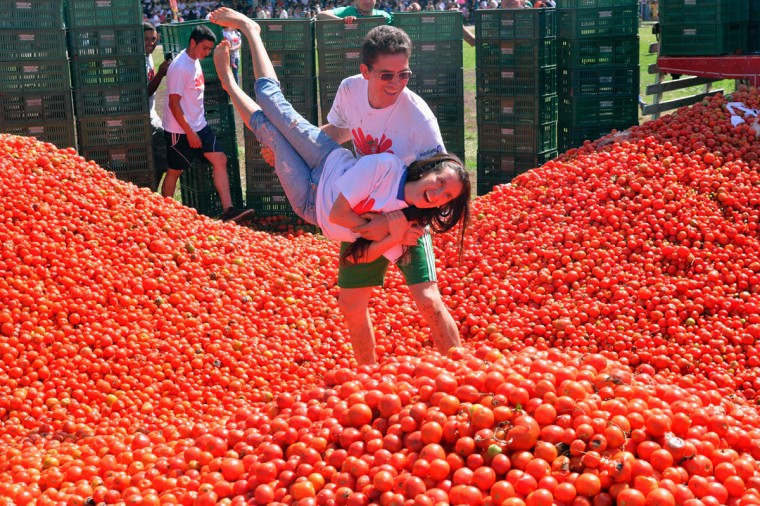 """A couple participates in the 10th annual tomato fight festival, known as """"tomatina"""", in Sutamarchan, Boyaca department, Colombia, on June 5, 2016. (GUILLERMO LEGARIA/AFP/Getty Images)"""