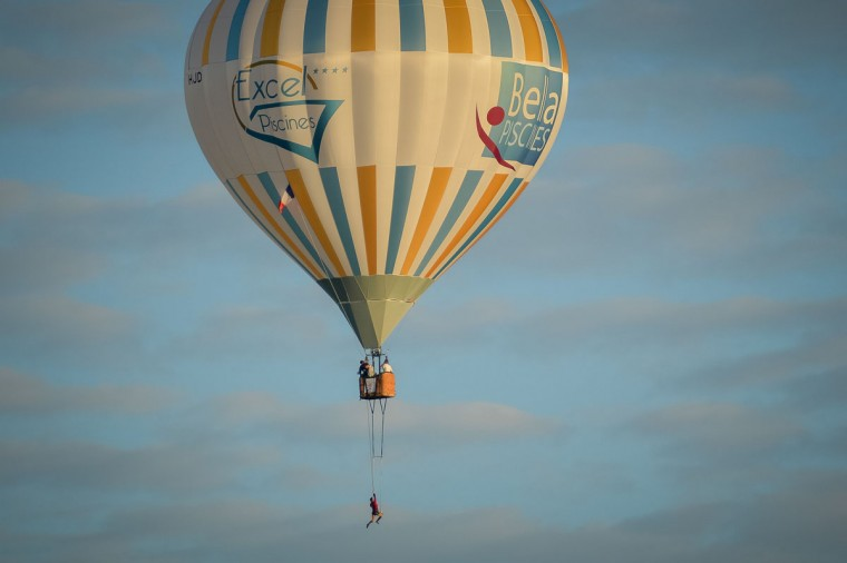French trapeze artist Isabelle Ponsot performs while hanging from a hot air balloon above Chatellerault on June 22, 2016. (GUILLAUME SOUVANT/AFP/Getty Images)