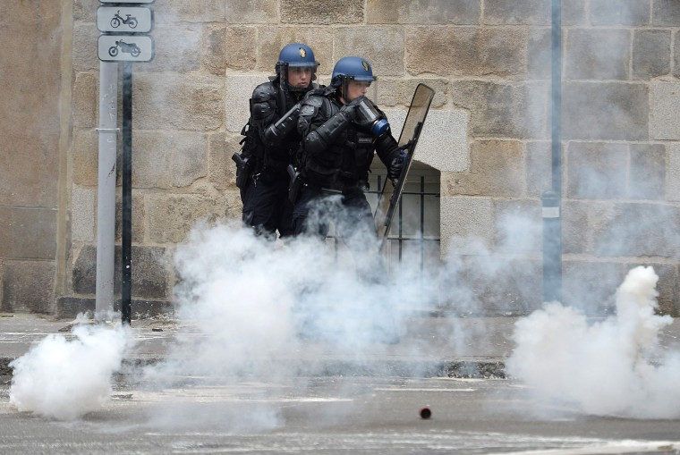 French riot police officers stand through smoke during clashes with protesters during a demonstration against the government's labour market reforms on June 2, 2016 in Nantes, western France. More demonstrations against the reforms which the government says are designed to make France more business-friendly -- were set to take place in major cities on June 2 and nuclear power workers were back on strike at 16 of the country's 19 power stations. (Jean-Sebastien Evrard/AFP/Getty Images)