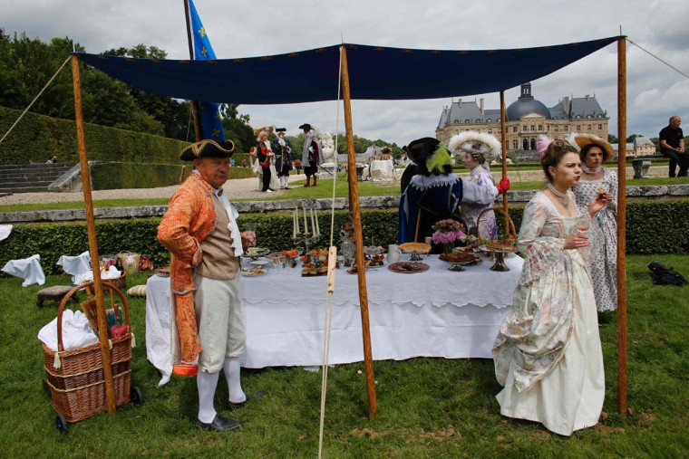 People wearing period costumes take part in a picnic in the gardens of the Chateau de Vaux-le-Vicomte (Vaux-le-Vicomte castle) in Maincy near Paris on June 26, 2016, during the annual Grand Siecle day event, a rendez-vous for costume passionates. (AFP PHOTO / MATTHIEU ALEXANDRE)