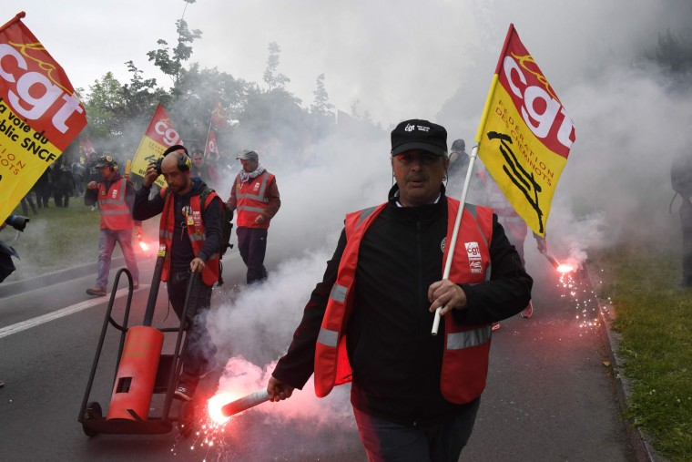 Protesters hold CGT (Labour General Confederation) flags during a rally against the government's labour market reforms in Rennes, northwestern France, on June 2, 2016. Thousands took to the streets across the country on Thursday in the latest demonstrations against the labour law reforms, which the government says are designed to make France more business-friendly. In Rennes, the police charged the protesters with the help of vehicles, leaving several injured. (Damien Meyer/AFP/Getty Images)