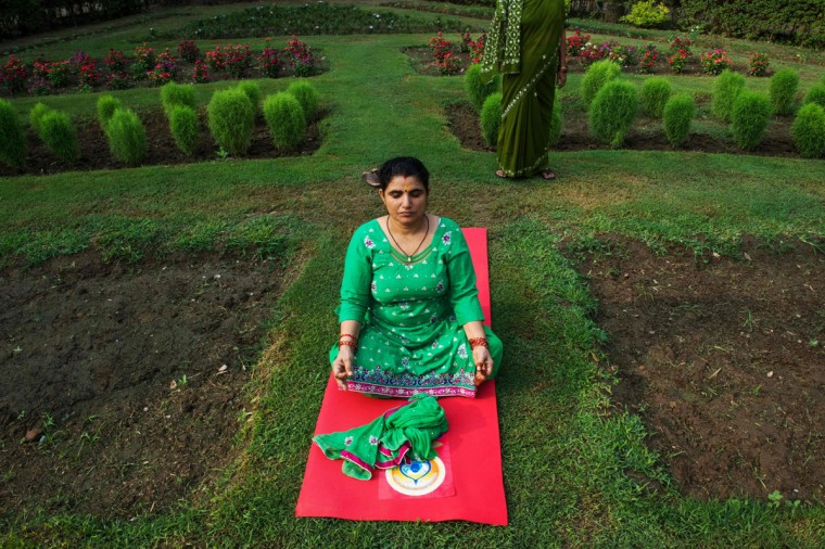 An Indian Yoga practitioner sits away from others as she participates in a morning yoga session to mark International Yoga Day in Lodhi Gardens in New Delhi on June 21, 2016 / (AFP PHOTO / ROBERTO SCHMIDT)