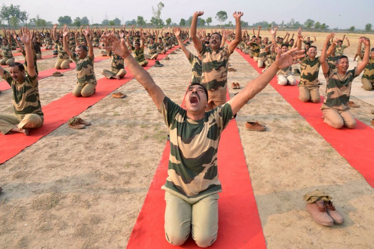 Indian Border Security Force (BSF) personnel take part in a yoga session on International Yoga Day at BSF headquarters in Khasa on the outskirts of Amritsar on June 21, 2016. Yoga, which means union in Sanskrit, is a family of ancient spiritual practices and also a school of spiritual thought from the South East Asian continent, where it remains a vibrant living tradition and is seen as a means of enlightenment. (AFP PHOTO / NARINDER NANU)