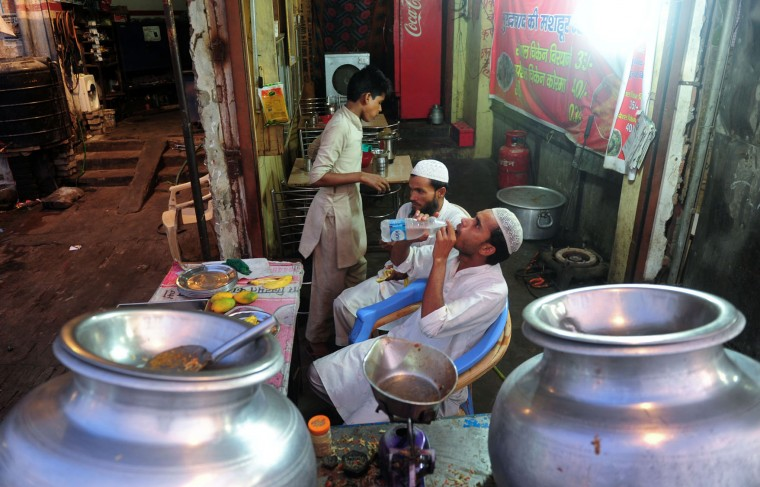 Indian Muslim shopkeepers break their fast at their place of work during the fasting month of Ramadan in Allahabad on June 17, 2016. Muslims throughout the world are marking the month of Ramadan, the holiest month in the Islamic calendar during which devotees fast from dawn till dusk. (Sanjay Kanojia/AFP/Getty Images)