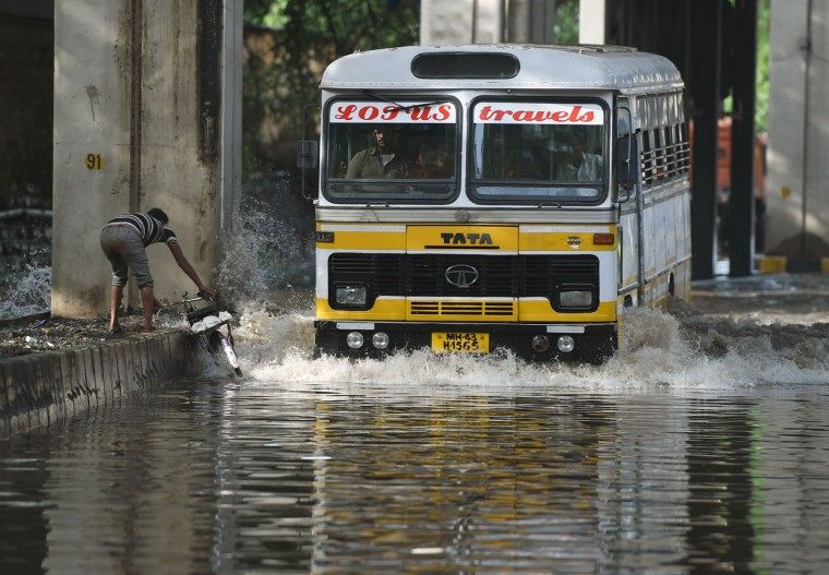 An Indian cyclist attempts to move onto a divider as a bus drives through a flooded street after heavy monsoon rain showers in Mumbai on June 21, 2016. (Punit Paranjpe/AFP/Getty Images)