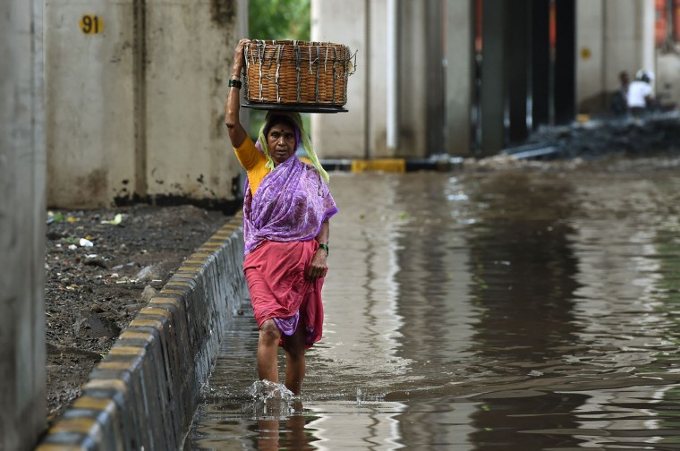An Indian pedestrian carries a basket on her head as she wades through a flooded street after heavy rain showers in Mumbai on June 21, 2016. (Punit Paranjpe/AFP/Getty Images)