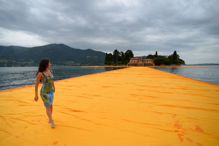 """A woman walks on the monumental installation """"The Floating Piers"""" created by artist Christo Vladimirov Javacheff and Jeanne-Claude, on June 16, 2016 during a press preview at the lake Iseo, northern Italy. (FILIPPO MONTEFORTE/AFP/Getty Images)"""